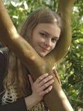 一个年轻美丽的女孩拿着一棵树的树干在她的胳膊和微笑的 库存图片