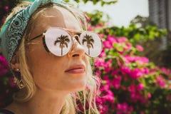 一个年轻美丽的女孩的特写镜头画象玻璃的与热带棕榈的反射 夏天休息现代游人 免版税图库摄影