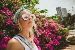 一个年轻美丽的女孩的特写镜头画象玻璃的与热带棕榈的反射 夏天休息现代游人 免版税库存照片