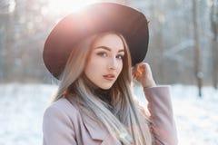 一个年轻美丽的女孩的画象黑帽会议的在一个冬天da 库存照片