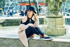 一个年轻美丽的时髦的女人的画象,摆在老欧洲城市的街道上的女孩 免版税库存图片