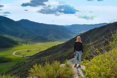 一个年轻美丽的白肤金发的女孩站立在t的峭壁边缘 图库摄影