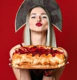 一个年轻美丽的金发碧眼的女人的画象拿着一个可口自创樱桃饼的kokoshnik的 库存照片