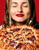 一个年轻美丽的金发碧眼的女人的画象拿着一个可口自创莓果饼的头巾的 库存图片