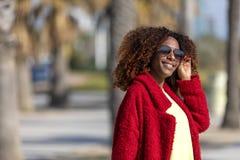 一个年轻美好的卷曲妇女身分的正面图在微笑的道路的,当看照相机在好日子时 免版税库存图片