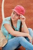 一个年轻聪慧的女孩爱体育 棒球帽的运动的女孩 库存照片