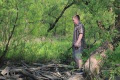 一个年轻肥满人在一棵佝偻病树的树干站立 在防风林附近 在鲜绿色的叶子中的公园 免版税库存照片