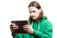 一个年轻英俊的人的画象看他的数字式片剂的一绿色有冠乌鸦的 生活方式、人们和技术概念 库存照片