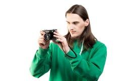 一个年轻英俊的人的画象看在白色背景的绿色有冠乌鸦的照相机 生活方式、人们和技术 免版税库存图片