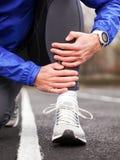 一个年轻赛跑者的播种的射击在痛苦中的握他的腿 库存照片