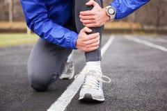 一个年轻赛跑者的播种的射击在痛苦中的握他的腿 免版税库存照片