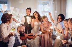 一个年轻跳舞和唱歌在一个结婚宴会的新娘、新郎和其他客人 免版税库存照片