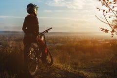一个年轻车手的画象在一个正面盔甲面具和手套的充分的保护的在自行车 免版税库存图片