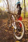 一个年轻车手的画象在一个正面盔甲面具和手套的充分的保护的在自行车 库存照片