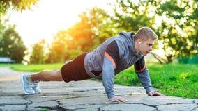 一个年轻运动人做俯卧撑 一个肌肉和坚强的人训练 本质上在公园在夏天 力量 库存图片