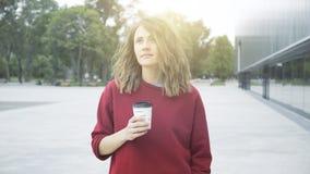 一个年轻逗人喜爱的偶然深色的女孩早晨喝咖啡外面 图库摄影