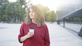 一个年轻逗人喜爱的偶然深色的女孩早晨喝咖啡外面 库存图片
