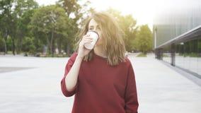 一个年轻逗人喜爱的偶然深色的女孩早晨喝咖啡外面 免版税库存图片