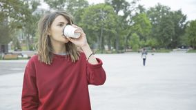 一个年轻逗人喜爱的偶然深色的女孩早晨喝咖啡户外 免版税库存图片