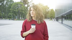 一个年轻逗人喜爱的偶然深色的女孩早晨喝咖啡户外 库存图片