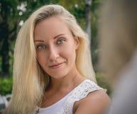 一个年轻金发碧眼的女人的画象一根白色女衬衫和流动的头发的,坐在有一个美丽的女朋友的庭院里 库存照片
