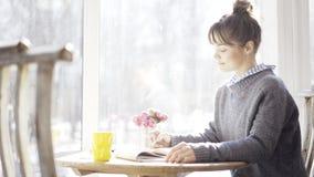 一个年轻镇静深色的女孩调查在咖啡馆的一个笔记本 库存照片