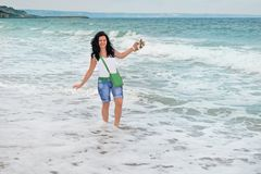 一个年轻长发女孩在波浪中站立在海 在黑海的岸的白海泡沫在保加利亚 免版税图库摄影
