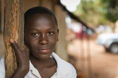 一个年轻非洲男孩的画象他的家入口的在Nhacra镇在几内亚比绍 库存图片