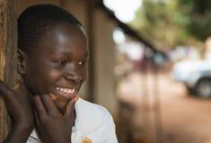 一个年轻非洲男孩的画象他的家入口的在Nhacra镇在几内亚比绍 免版税库存照片