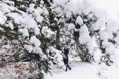 一个年轻,俏丽的女孩摆在一棵大积雪的杉木前面下 库存照片