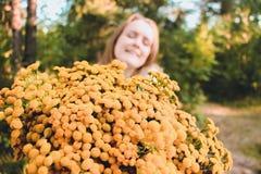一个年轻,美丽和愉快的女孩接受黄色野花一巨大的bougette作为礼物 库存照片