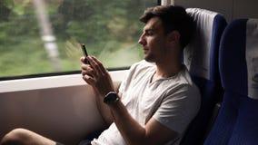 一个年轻,英俊的人的侧视图乘现代火车移动 坐在窗口旁边和看他的手机 股票视频