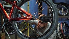 一个年轻mahanic定象自行车车轮她的修理车间 股票录像