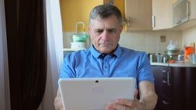 一个年迈的男性的Portait在家坐并且使用一台白色片剂个人计算机 免版税库存照片