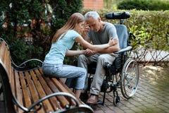 一个年长人在轮椅坐 在长凳旁边是他的女儿 他们握手 免版税库存图片