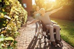 一个年长人在轮椅坐 女孩滚动它,并且他们无所事事  他们走外面并且笑 免版税库存图片