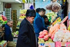 一个年长人在Je选择水果和蔬菜在市场上 免版税库存图片
