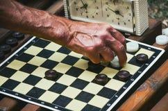一个年长人的手棋枰背景的 库存照片
