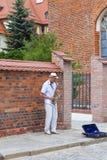 一个年长人,音乐家,播放金钱的萨克斯管在街道上 库存照片