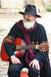一个年长以色列人-有一把吉他的一位街道艺术家在他的手上 库存图片