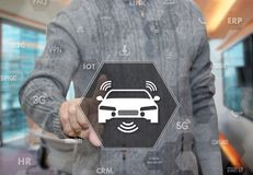 一个年长领抚恤金者选择汽车无线上网,在汽车的Wi-Fi在迷离办公室背景的触摸屏上 免版税库存图片