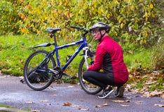 一个年长骑自行车者在贝尔法斯特蹲下下来进行连续修理到他的自行车在河Lagan拉船路 免版税库存照片