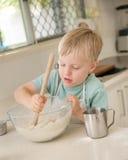 一个幼儿在一个国内厨房里烹调。 免版税图库摄影