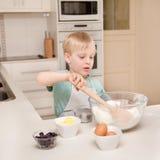一个幼儿在一个国内厨房里烹调。 库存照片
