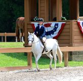 一个幼儿骑在Germantown慈善马展示的一匹马 图库摄影