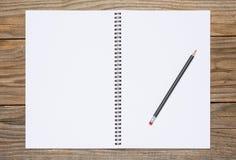 一个开放写生簿的空白页与一支黑铅笔的 图库摄影