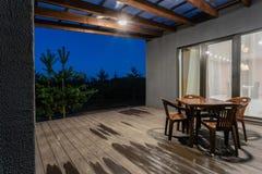 一个开放游廊的侧视图在一个现代森林村庄前面的 在日落下的杉木年轻森林在发出光线 免版税库存照片