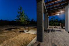 一个开放游廊的侧视图在一个现代森林村庄前面的 在日落下的杉木年轻森林在发出光线 图库摄影