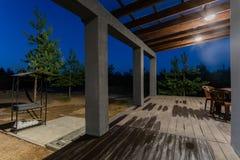 一个开放游廊的侧视图在一个现代森林村庄前面的 在日落下的杉木年轻森林在发出光线 免版税库存图片