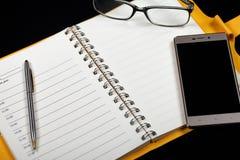 一个开放笔记本、玻璃、笔和智能手机的顶视图在黑背景 免版税库存图片